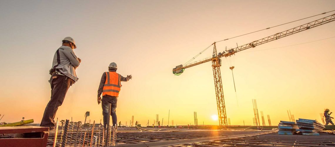 silhouette group of worker and civil engineer  in safety uniform install reinforced steel column in construction site during sunset time industrial concept
