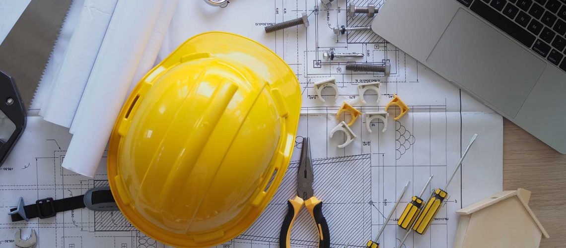 Contractor's desk and engineering team. There are blueprints, hard hats and various accessories.